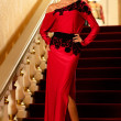 Beautiful young woman in long evening dress standing on a steps in luxury interior — Stockfoto
