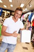 Happy handsome young with with shopping bag in sport outlet — Zdjęcie stockowe