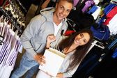 Happy young couple with shopping bag in sportswear store — Стоковое фото