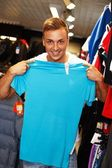 Handsome young man choosing t-shirt in a sport outlet — Zdjęcie stockowe