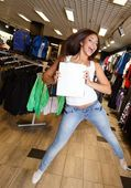 Beautiful happy brunette girl with shopping bag jumping in a sport outlet — Zdjęcie stockowe