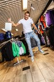 Handsome young man with shopping bag jumping in sport outlet — Stockfoto