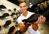 Young handsome man choosing sport footwear in sport outlet — Stock Photo