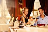 Beautiful young couple with glasses of red wine in luxury restaurant — Foto Stock