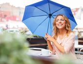 Girl with blue umbrella sitting in summer cafe — Foto Stock