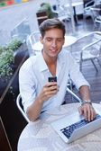 Handsome young man with laptop and mobile phone in a summer cafe — Stock Photo