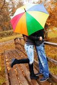 Happy middle-aged couple with umbrella outdoors — Stock Photo