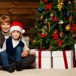 Mother and her boy in Santa hat with gift box under christmas tree — Stock Photo #33870037