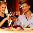 Beautiful young couple with glasses of red wine in luxury restaurant — Stock Photo #33870071