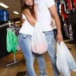 Happy young couple with shopping bags in sportswear store — Stock Photo