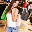 Beautiful happy brunette girl with shopping bag in a sport outlet — Zdjęcie stockowe