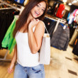 Beautiful happy brunette girl with shopping bag in a sport outlet — Foto Stock