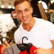 Handsome young man choosing sports wear in a sport outlet — Stockfoto
