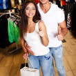 Happy young couple with shopping bag in sportswear store — Stock Photo