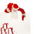 Santa Claus with many gift boxes and blank notice board — Stock Photo