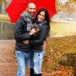 Happy middle-aged couple with umbrella outdoors on beautiful rainy autumn day — Stockfoto
