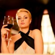 Beautiful blond woman in evening with glass of red wine  — Stock Photo