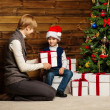 Mother and her lIttle boy in Santa hat with gift box under christmas tree in wooden house interior — Stock Photo