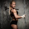 Beautiful muscular bodybuilder woman holding hammer and chains — Stock Photo