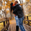 Happy middle-aged couple kissing outdoors on beautiful autumn day — Photo