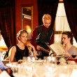 Group of young friends with menus choosing in a luxury restaurant — Stockfoto