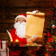 Santa Claus in wooden home interior holding blank wish list scroll — Stock Photo #36293167