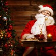 Santa Claus talking over phone in wooden home interior — Stock Photo