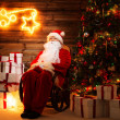 Santa Claus sitting on rocking chair in wooden home interior with illuminated decoration on a wall — Stock Photo