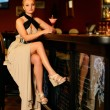 Beautiful blond woman in evening dress sitting near bar counter with cocktail — Stock Photo