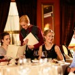 Stock Photo: Group of young friends with menus choosing in luxury restaurant