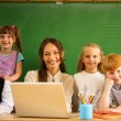Group of happy classmates with their teacher in class near blackboard  — Stock Photo