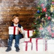 Stock Photo: LIttle boy opening gift box under christmas tree in wooden house interior