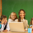 Group of happy classmates with their teacher in class near blackboard — Stock Photo #36293451