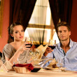Beautiful young couple with glasses of wine in restaurant — Stock Photo