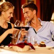 Beautiful young couple with glasses of red wine in luxury restaurant — ストック写真