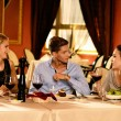 Young friends with glasses of red wine having conversation in a luxury restaurant — 图库照片