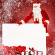 Santa Claus with sack full of gift boxes and blank notice board — Stock Photo