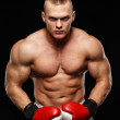 Handsome muscular young man wearing boxing gloves — Stock Photo