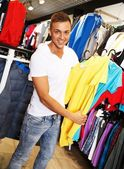 Handsome young man choosing t-shirt in a sport outlet — Stockfoto