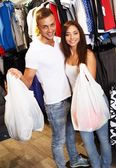 Happy young couple with shopping bags in sportswear store — Zdjęcie stockowe