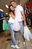 Happy young couple with shopping bags in sportswear store — Stockfoto