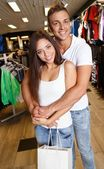 Happy young couple with shopping bag in sportswear store — Zdjęcie stockowe