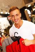 Handsome young man choosing sports wear in a sport outlet — Zdjęcie stockowe