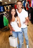 Happy young couple with shopping bag in sportswear store — Stockfoto