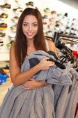 Beautiful happy brunette girl with hoodies in sport outlet — Stock Photo