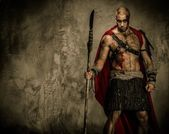 Wounded gladiator in red coat holding spear — Stock Photo