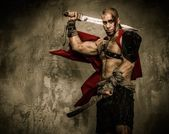 Wounded gladiator with two swords covered in blood — Stock Photo