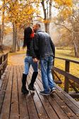 Happy middle-aged couple kissing outdoors on beautiful autumn day — Stock Photo