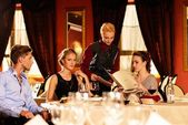 Group of young friends with menus choosing in a luxury restaurant — Stok fotoğraf
