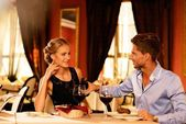 Young couple with bottle of red wine in luxury restaurant — Stock Photo